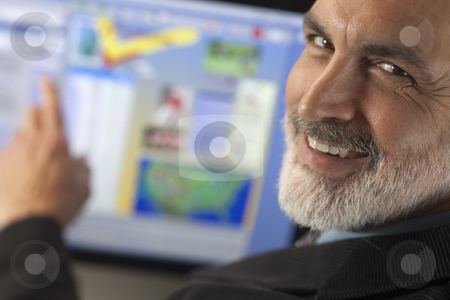 Businessman Smiling and Pointing to Computer Monitor stock photo, Close-up portrait of a businessman smiling over his shoulder at the camera while pointing to a computer monitor. Horizontal shot. by Edward Bock
