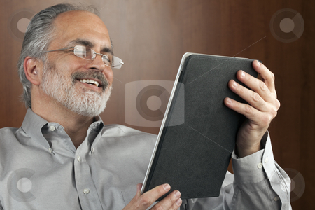 Businessman Reading From a Tablet stock photo, Portrait of a smiling businessman reading information from an electronic tablet. Horizontal shot. by Edward Bock