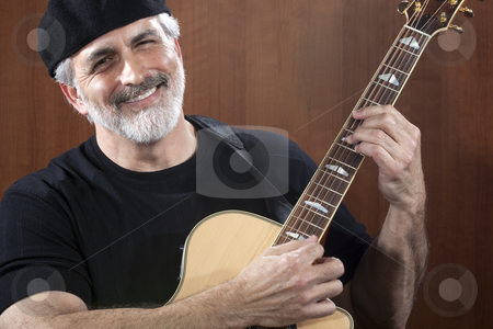 Middle-Aged Man With Acoustic Guitar stock photo, Portrait of a middle-aged man wearing a black beret and t-shirt and playing an acoustic guitar. He is smiling at the camera. Horizontal shot. by Edward Bock