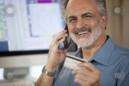 Businessman Paying Over Phone With Credit Card stock photo, A businessman holding up a credit card and making a payment on his cellphone with a computer monitor in the background. Horizontal shot. by Edward Bock