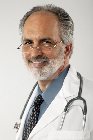 Doctor With Glasses and Lab Coat stock photo, Portrait of a doctor wearing glasses and a white lab coat, with a stethoscope draped around his neck.  He is looking at the camera and smiling. Vertical format. by Edward Bock