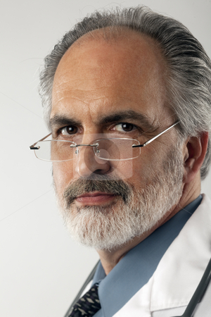 Doctor With Glasses and Lab Coat stock photo, Close-up portrait of a doctor wearing glasses and a white lab coat.  He is looking at the camera with a serious expression. Vertical format. by Edward Bock