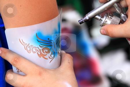 Air brush tatoo stock photo, Creating an air brush tatoo on a youn gilrs arm by Henrik Lehnerer