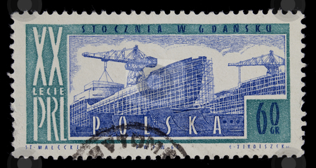 Shipyard on vintage post stamp from Poland stock photo, POLAND 1964 - vintage canceled post stamp with engraving of shipyard in Gdansk, commemorating 20th anniversary of Polish People Republic, later a birth place of solidarity movement and labor union, black background by Marek Uliasz