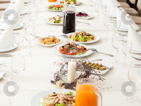 Served restaurant table stock photo, Long served restaurant table eith snacks and salads by Ruta Balciunaite