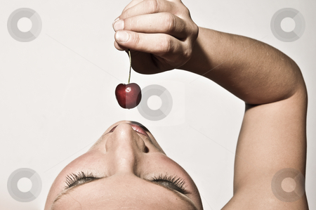 Woman Sensually Tasting A Cherry stock photo, Upper View Closeup Of A Woman Sensually Tasting A Cherry by Nick Fingerhut