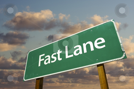 Fast Lane Green Road Sign Over Clouds stock photo, Fast Lane Green Road Sign Over Dramatic Clouds and Sky. by Andy Dean