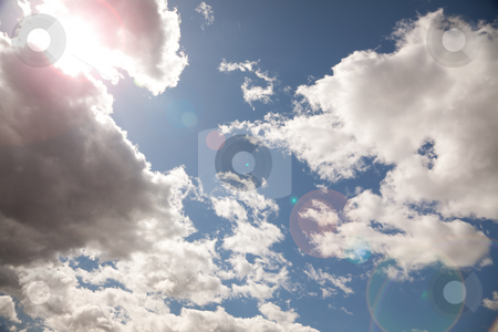 Beautiful Sky and Clouds with Lens Flare stock photo, Beautiful Sky and Clouds on a Deep Blue Sky - Lens Flare Enhanced. by Andy Dean