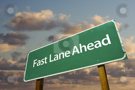 Fast Lane Ahead Green Road Sign Over Clouds stock photo, Fast Lane Ahead Green Road Sign Over Dramatic Clouds and Sky. by Andy Dean