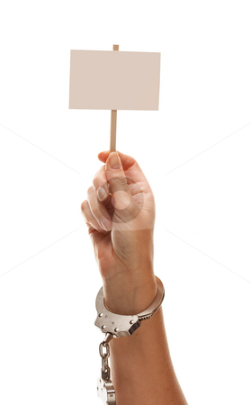 Handcuffed Woman Holding Blank White Sign Isolated on White stock photo, Handcuffed Woman Holding Blank White Sign Isolated on a White Background - Ready for Your Own Message. by Andy Dean