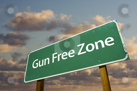 Gun Free Zone Green Road Sign and Clouds stock photo, Gun Free Zone Green Road Sign In Front of Dramatic Clouds and Sky. by Andy Dean