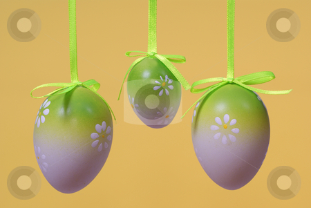 Easter eggs stock photo, hang eggs on ribbon made on yellow background by Jolanta Dabrowska