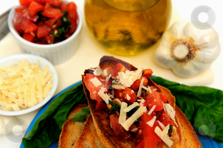 Bruschetta And Olive Oil stock photo, Bruschetta on a turquoise plate with toasted baguette slices and more tomato, basil, garlic and olive oil including grated asiago cheese in a small white containers by Lynn Bendickson