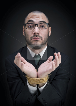 Puzzled businessman stock photo, A man on a suit shows his tied hands with a puzzled expression. by Ignacio Gonzalez Prado