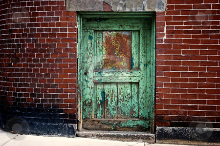 Green door stock photo, Old decaying green door in curved red brick wall by Stephen Orsillo