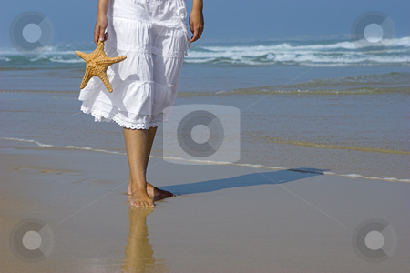 Starfish woman stock photo, Beautiful woman on the beach with a starfish on the hand by ikostudio