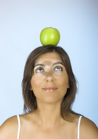 Apple on the head stock photo, Portrait of a young woman with a apple on the head by ikostudio