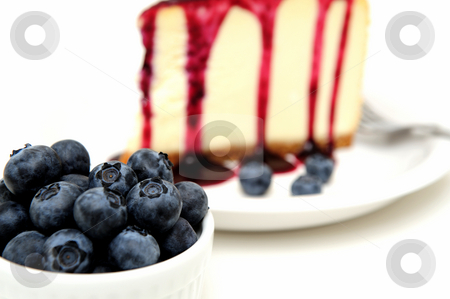 Fresh Blueberries And Cheesecake stock photo, Plain Cheesecake with a Blueberry sauce poured over the top with fresh berries on the plate next to the cake and topped with a mint leaf. by Lynn Bendickson