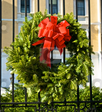 Holiday wreath stock photo, Christmas holiday wreath made of pine with red bow hangs on old iron fence  in the sunshine by Stephen Orsillo