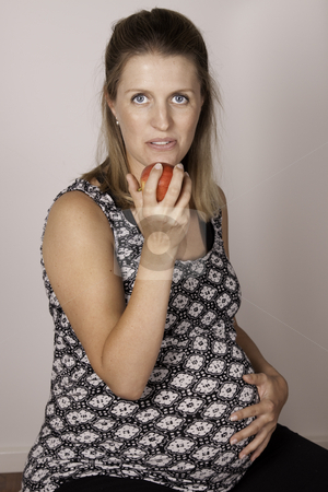 Pregnant diet stock photo, Pregnant woman showing how to eat healthy with an apple by Jandrie Lombard