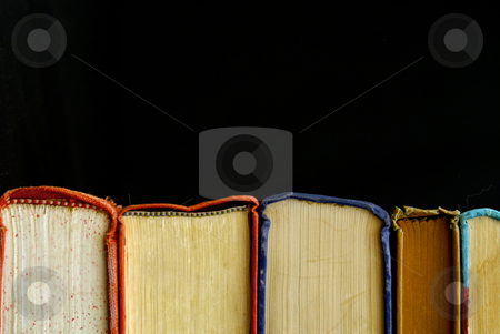 Book binding stock photo, Looking at row of books across the bindings against a black background by Stephen Orsillo