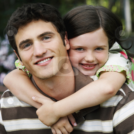 Cute Young Girl Hugging Young Man stock photo, Young girl wraps her arms around a young man from behind. They are both smiling towards the camera. Square shot. by Gerard Fritz