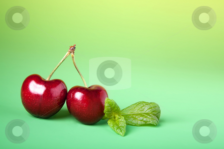 Cherry twins stock photo, Two perfect specimen of red cherries on a green background by Anneke