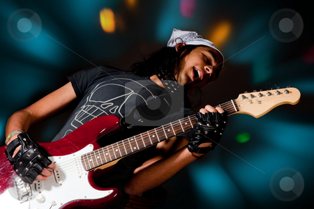 Spotlights stock photo, Young handsome rock singer against a dark background with spot lights by Anneke