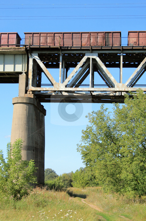 Train on the bridge stock photo, Freight train passing the steel bridge over the river by Jan Remisiewicz