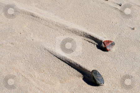 Two stones on the beach stock photo, Two stones with a sand trail behind them caused by wind by Jan Remisiewicz