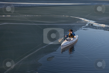Canoe paddling on ice covered lake stock photo, Paddling decked expedition canoe on a lake covered with dark soft ice, early spring by Marek Uliasz