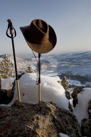 Trekking poles and hat in mountain scenery stock photo, Trekking poles and cowboy style hat in winter mountain scenery, Front Range of Rocky Mountains near Fort Collins, Colorado by Marek Uliasz
