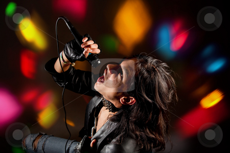 Rock singer stock photo, Young handsome rock singer against a dark background with spot lights by Anneke