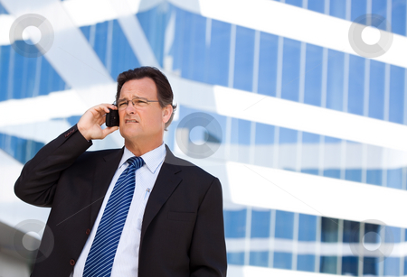 Concerned Businessman Talks on His Cell Phone stock photo, Concerned, Stressed Businessman Talks on His Cell Phone Outside of Corporate Building. by Andy Dean