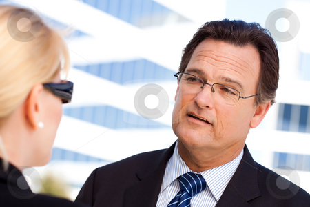 Businessman Talking with Female Colleague stock photo, Attentive, Handsome Businessman in Suit and Tie Talking with Female Colleague Outdoors. by Andy Dean