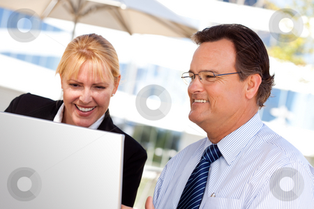 Businessman and Female Colleague Using Loptop Outdoors stock photo, Handsome Businessman Laughs While Working on the Laptop with Attractive Female Colleague Outdoors. by Andy Dean