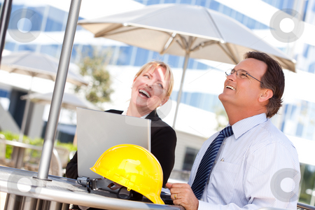 Businesswoman and Man Laughing While Working stock photo, Handsome Businessman and Attractive Businesswoman Laughing While Working on the Laptop Outdoors. by Andy Dean