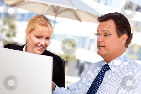 Businessman and Female Colleague Using Loptop Outdoors stock photo, Handsome Businessman Working on the Laptop with Attractive Female Colleague Outdoors. by Andy Dean