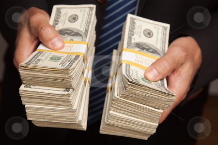 Businessman Handing Over Stacks of Money stock photo, Businessman Handing Over Stacks of Hundred Dollar Bills. by Andy Dean