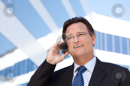 Businessman Smiles as He Talks on His Cell Phone stock photo, Confident, Handsome Businessman Smiles as He Talks on His Cell Phone Outdoors. by Andy Dean