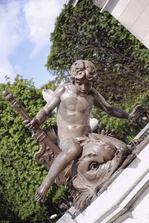 Bronze statue  stock photo, Bronze statue of a boy with fish, in paris france by Olivia Neacsu