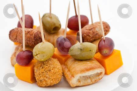 Party snacks. Mini sausage rolls, olives, scotch eggs, cheese an stock photo, Party snacks. Mini sausage rolls, olives, scotch eggs, cheese and red grapes on white plates by Robert Anthony
