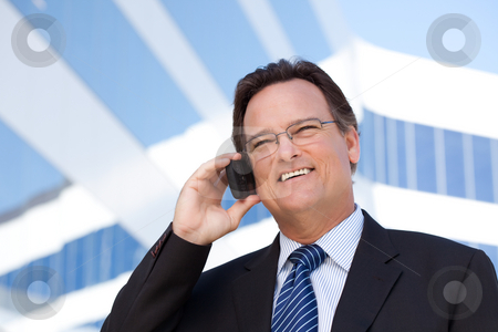 Businessman Smiles as He Talks on His Cell Phone stock photo, Confident, Handsome Businessman Smiles as He Talks on His Cell Phone. by Andy Dean