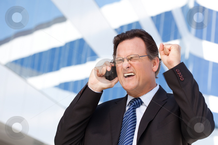 Excited Businessman on Cell Phone stock photo, Excited Businessman Using Cell Phone Clinches His Fist in Joy Outside of Corporate Building. by Andy Dean