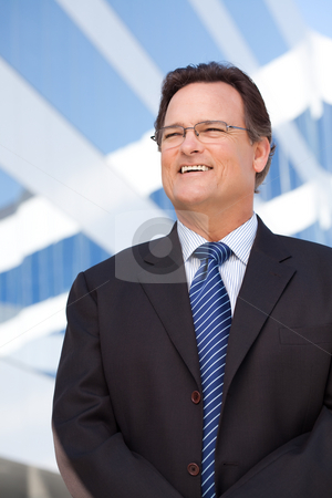 Handsome Businessman Smiling stock photo, Handsome Businessman Smiling in Suit and Tie Outside of Corporate Building. by Andy Dean