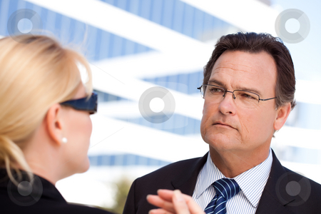 Businessman Listens to Female Colleague stock photo, Attentive Handsome Businessman in Suit and Tie Listens to Female Colleague Outdoors. by Andy Dean