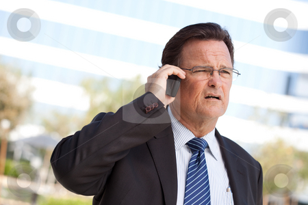 Concerned Businessman Talks on His Cell Phone stock photo, Concerned, Stressed Businessman Talks on His Cell Phone. by Andy Dean