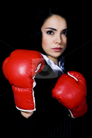 Tough Businesswoman stock photo, Stock image of businesswoman in fighting stance wearing boxing gloves over black background by iodrakon