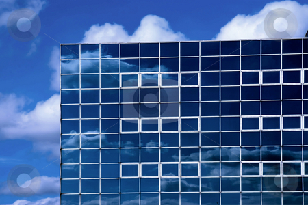 Modern glass office stock photo, The corner of a glass office block reflecting the sky and clouds. by Paul Phillips