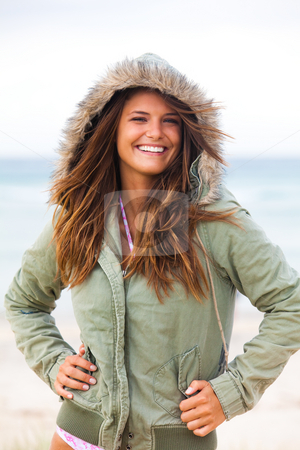 Attractive Young Woman Wearing a Coat stock photo, An attractive young woman is wearing a coat at the beach and standing with her hands on her hips. Vertical shot. by Angela Hawkey